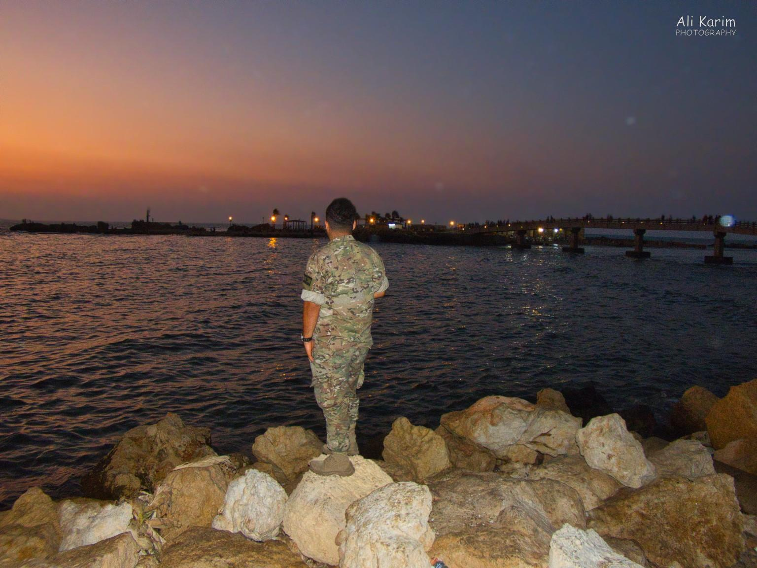 Beirut to Tripoli This soldier asked me to take his picture and send to him on WhatsApp; small island offshore linked by a bridge