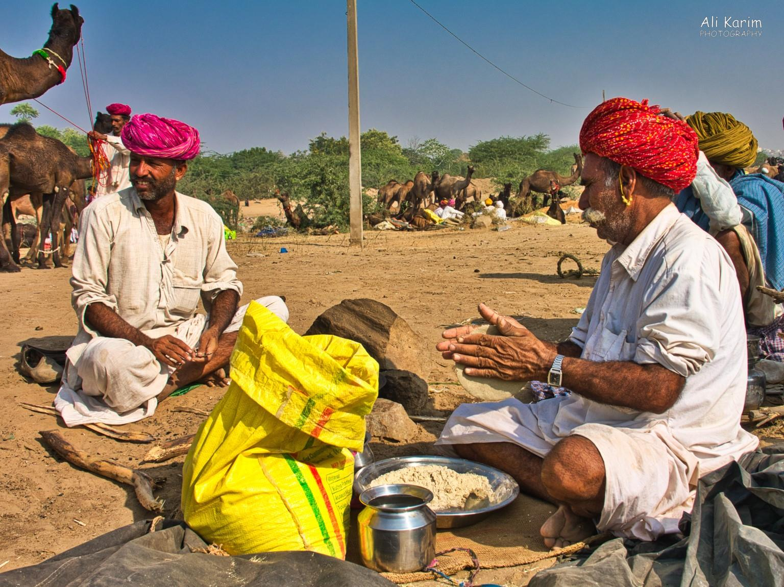 Pushkar, Rajasthan Making baajra roti's on a campfire behind the yellow flour bag