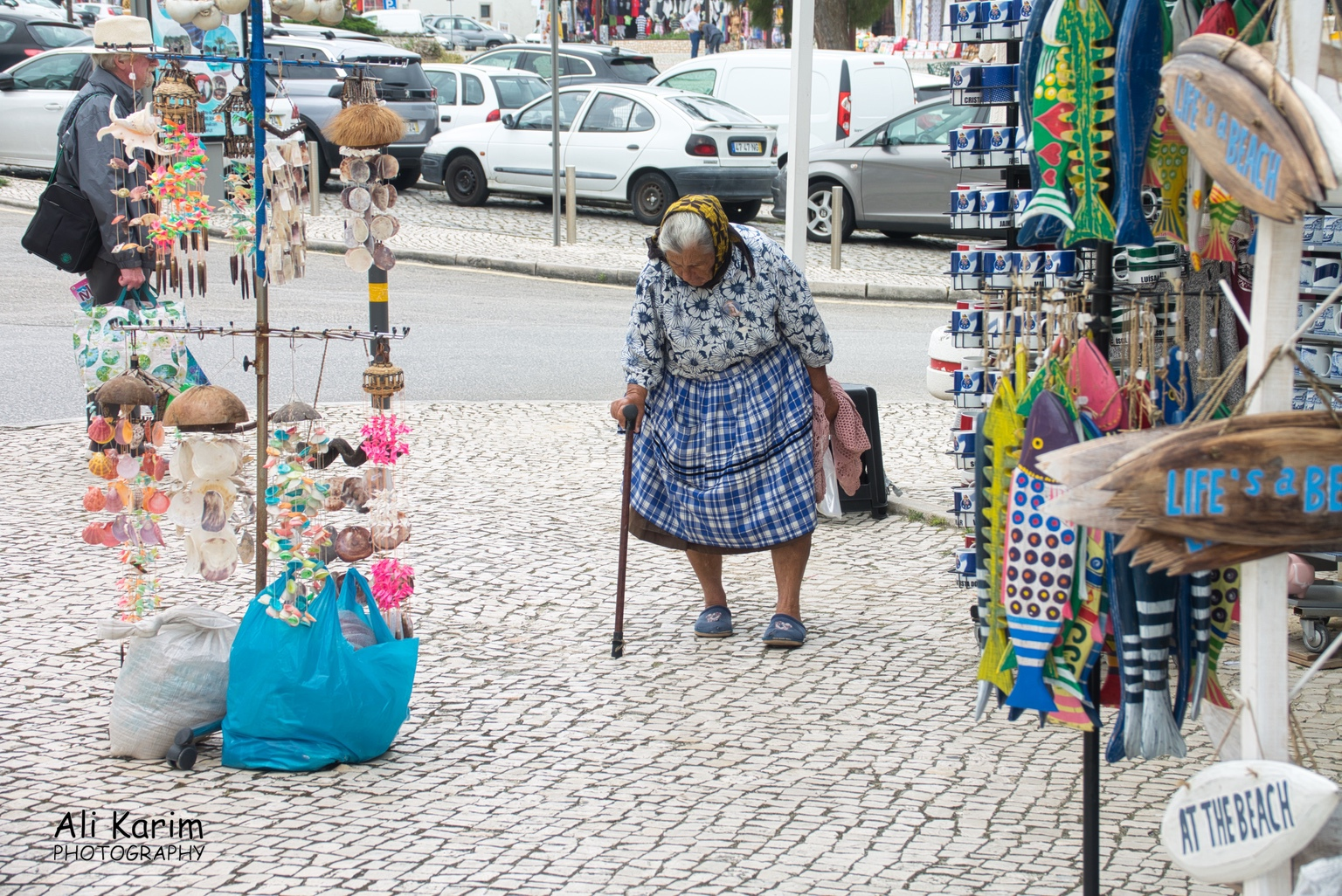 West of Lisbon Traditionally dressed lady, walking past the tourist shops