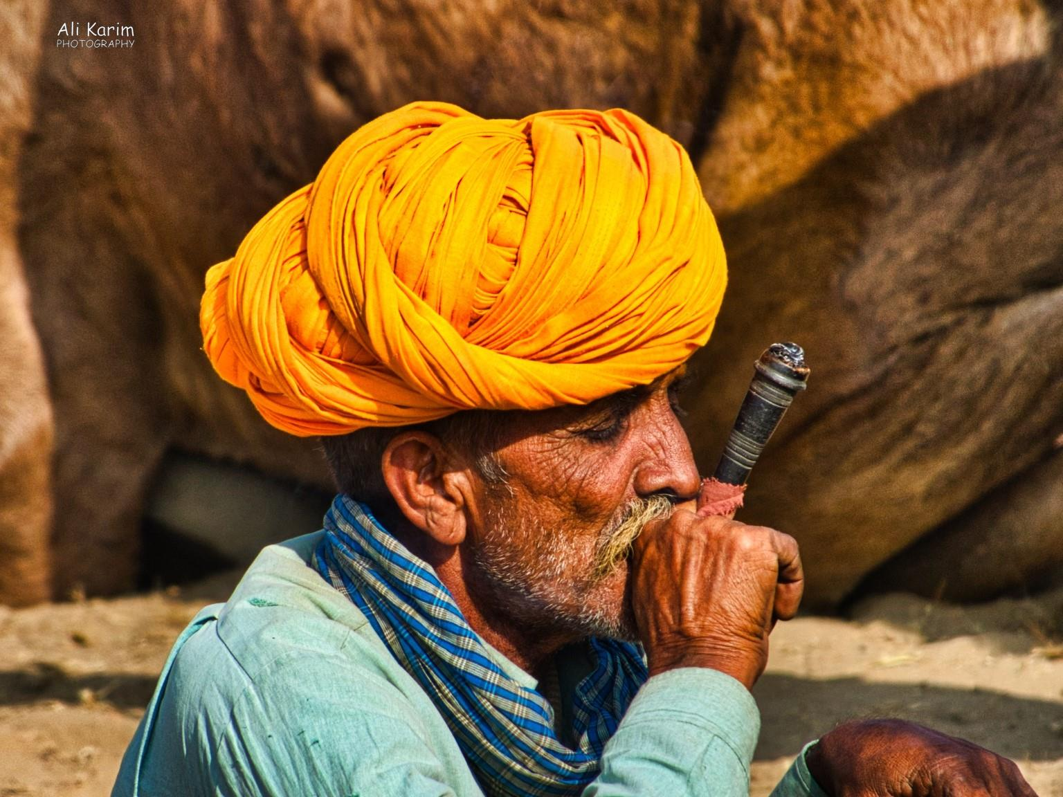 Pushkar, Rajasthan Passing the time smoking, while waiting for buyers for their camels