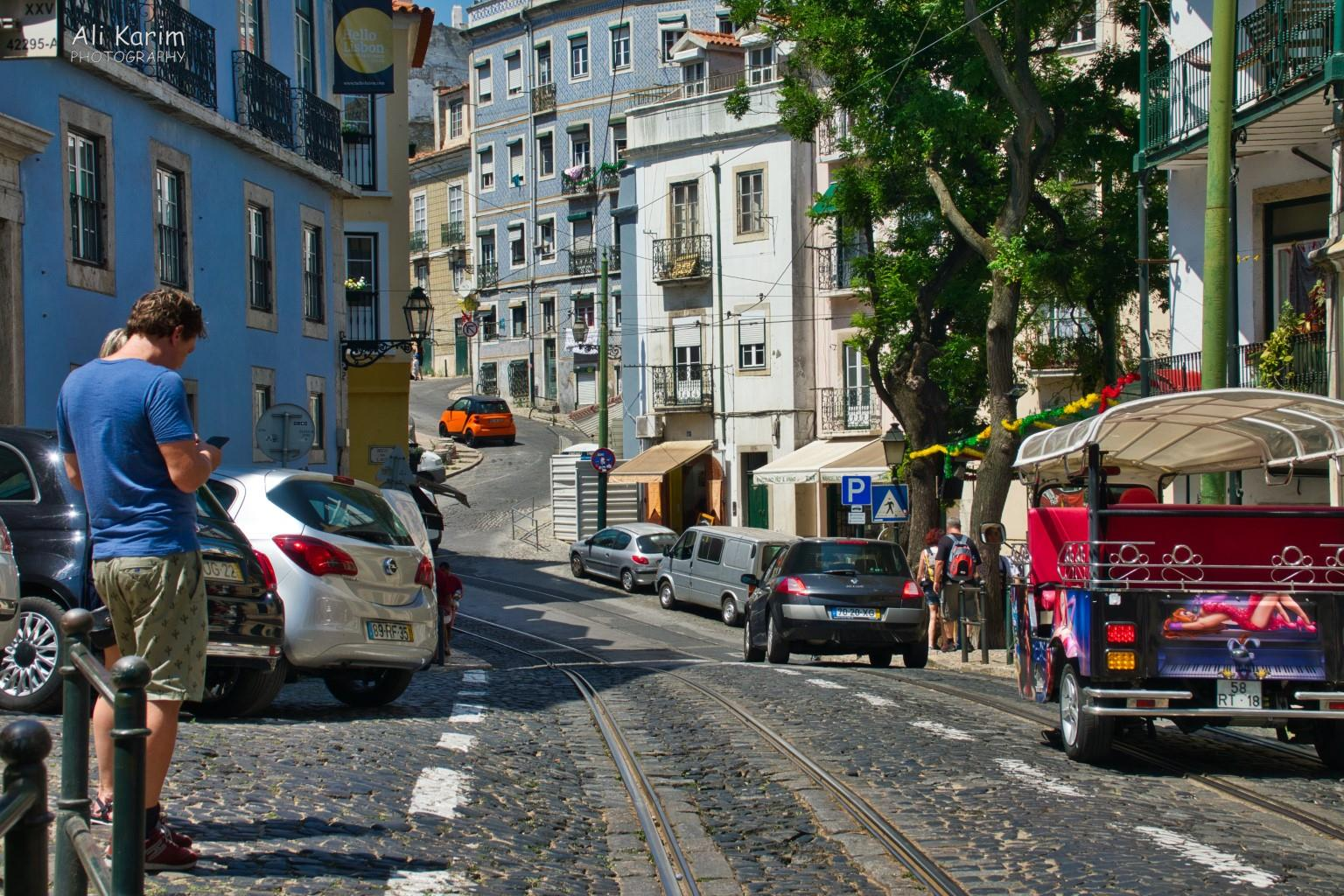 Lisbon Portugal: Narrow ancient cobblestone roads shared by trams, people and cars in Alfama