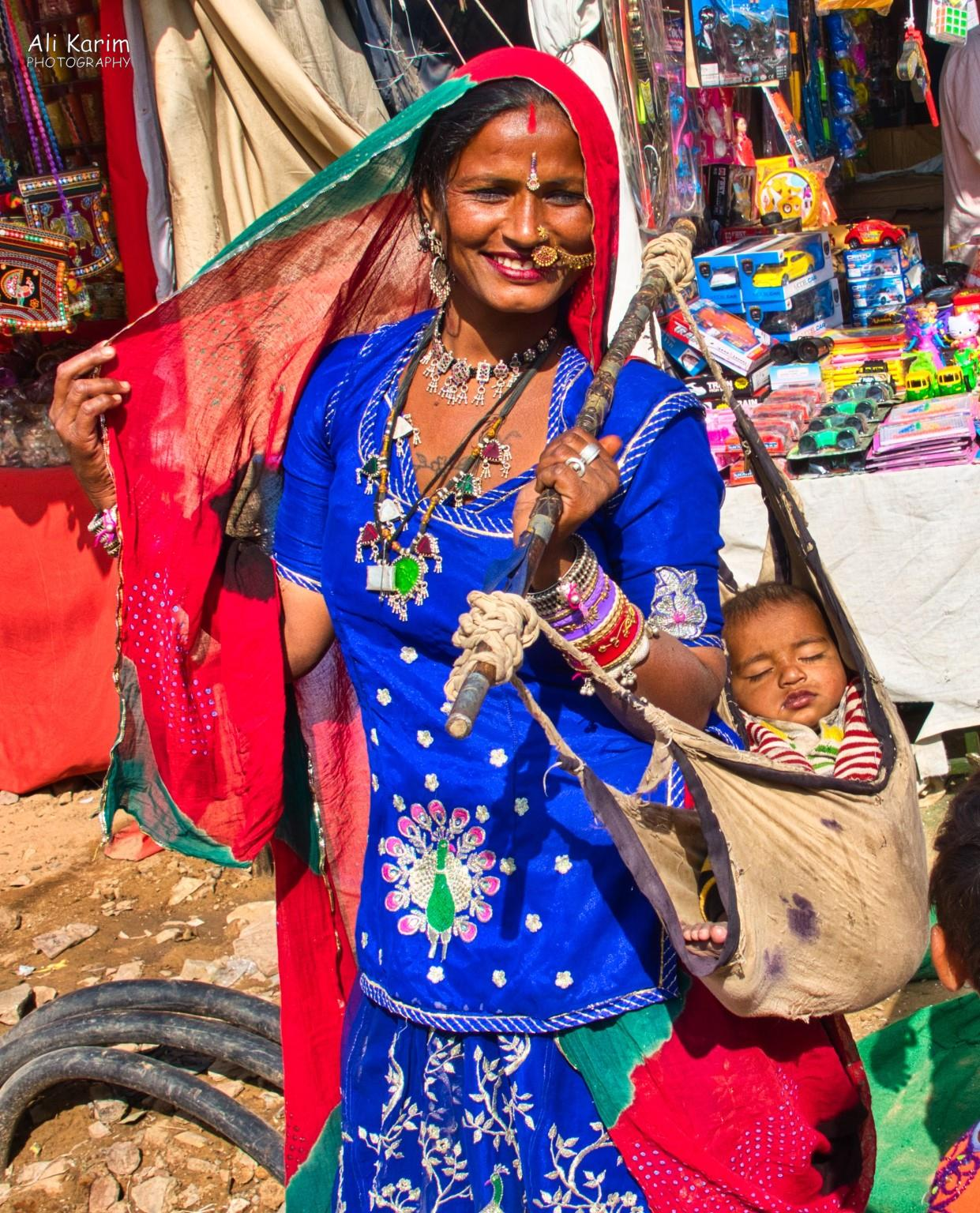 Pushkar, Rajasthan Tribal woman with her baby; interesting way to carry a baby around