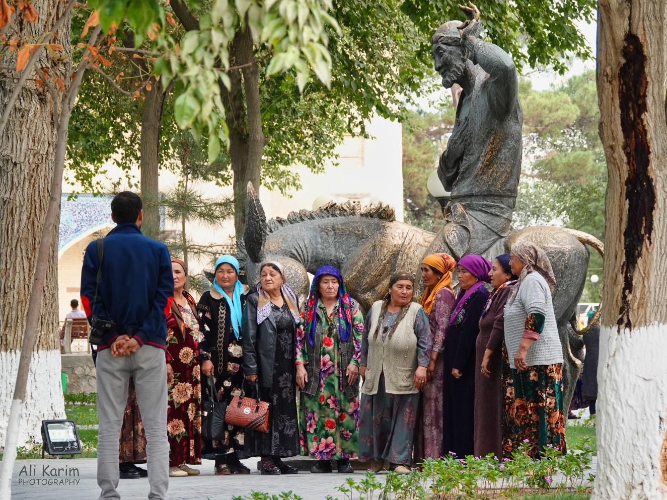 Bukhara, Oct 2019, Local tourists with the statue of Mulla Nasruddin Hodja on his donkey